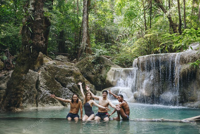 Group of diverse friends enjoying the waterfall