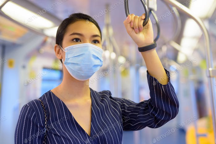 Young Asian businesswoman with mask for protection from corona virus outbreak riding the train