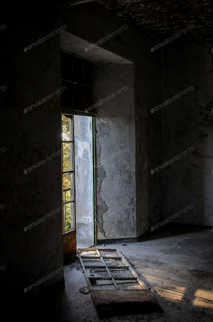 Abandoned room broken door and dramatic bright sunlight entering the place