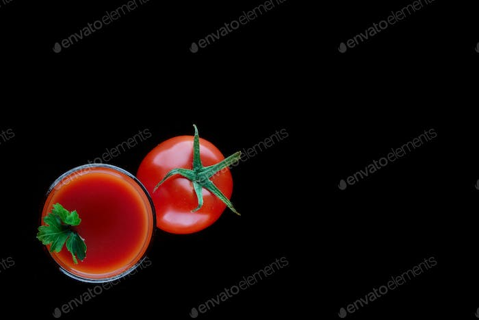 Glass of tomato juice with parsley and a tomato