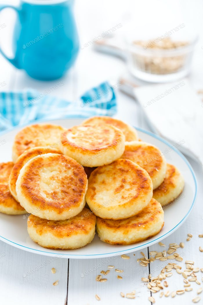 Cottage cheese pancakes with oats, syrniki on white rustic background