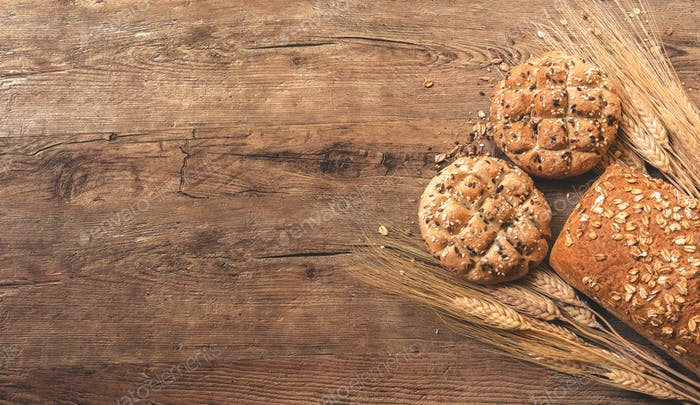 Bread and wheat on wooden background