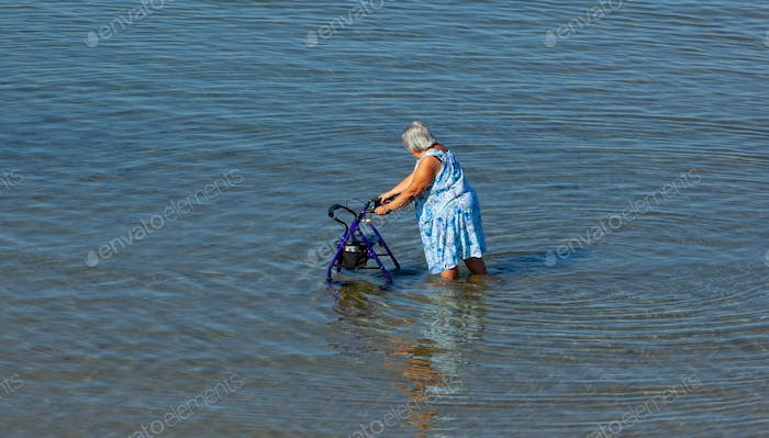Elderly lady walks with walker in the sea.