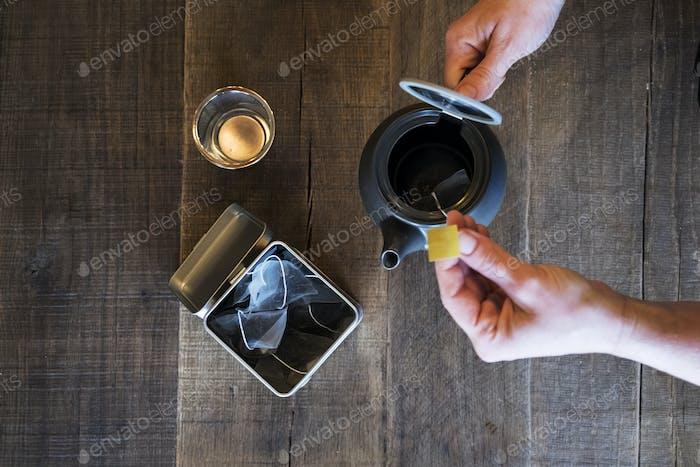 Hoher Winkel Nahaufnahme der Person Hinzufügen von Teebeutel zu kleinen schwarzen Teekanne.