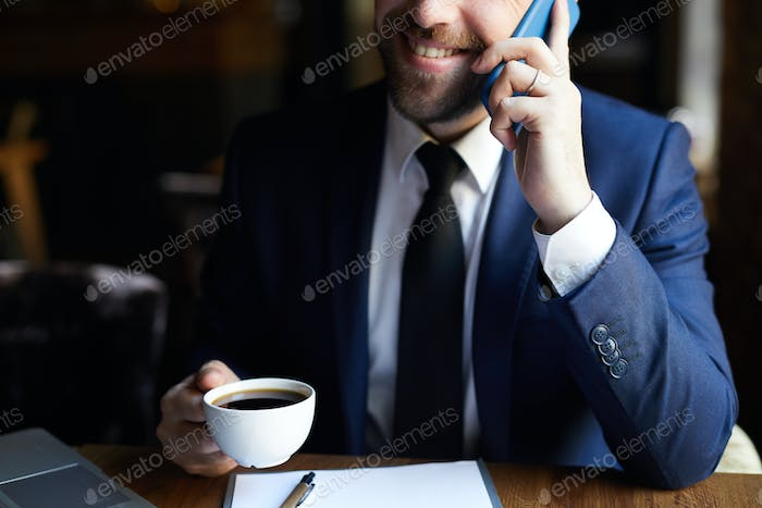 Positive businessman with coffee calling on phone