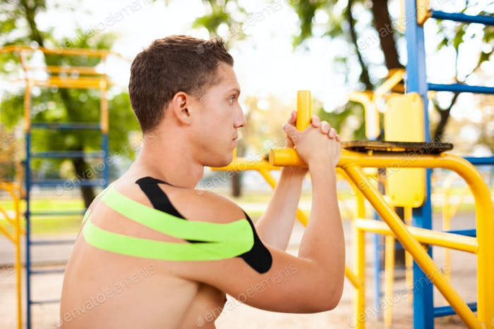Athlete with kinesiological tape posing at sports ground