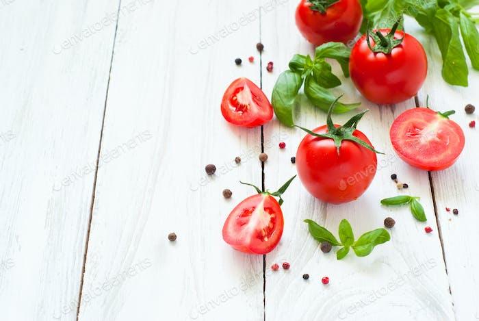 Tomaten, Basilikum und Knoblauch auf weißem Holztisch