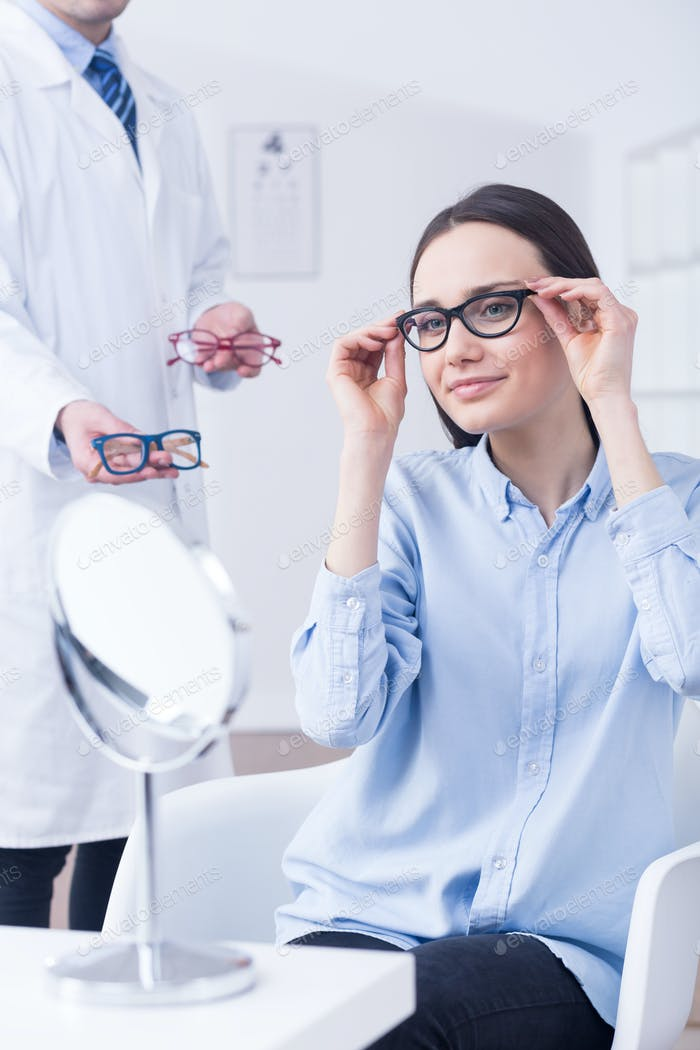 Optician and woman choosing eyeglasses