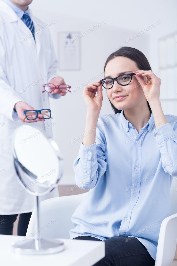 Optician and woman choosing eyeglasses