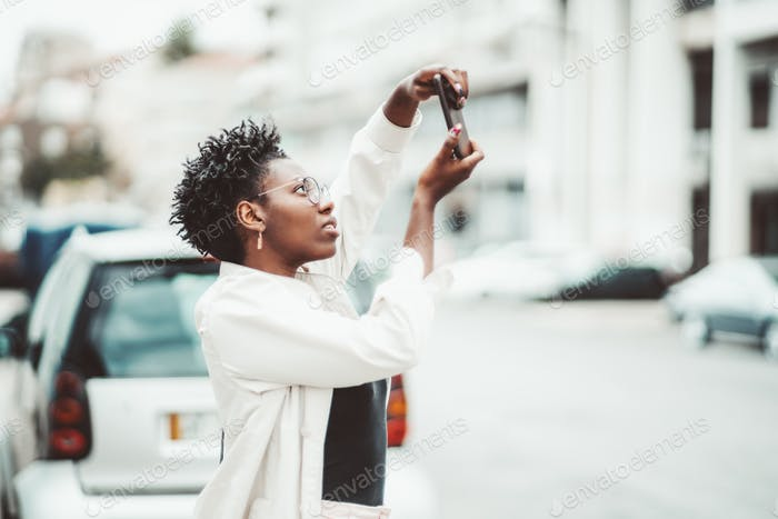 Afro girl photographing on cellphone