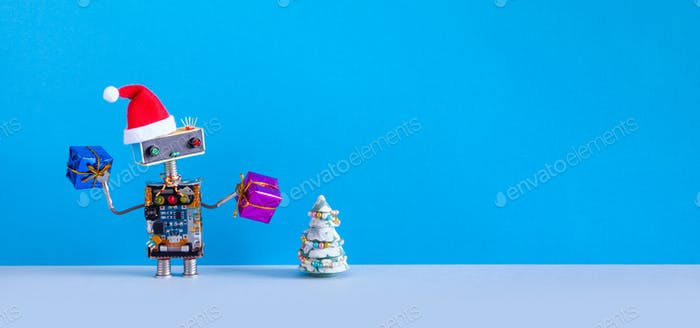 Toy Santa holds gift boxes. Robotic Xmas simplicity concept. blue wall, copy space.