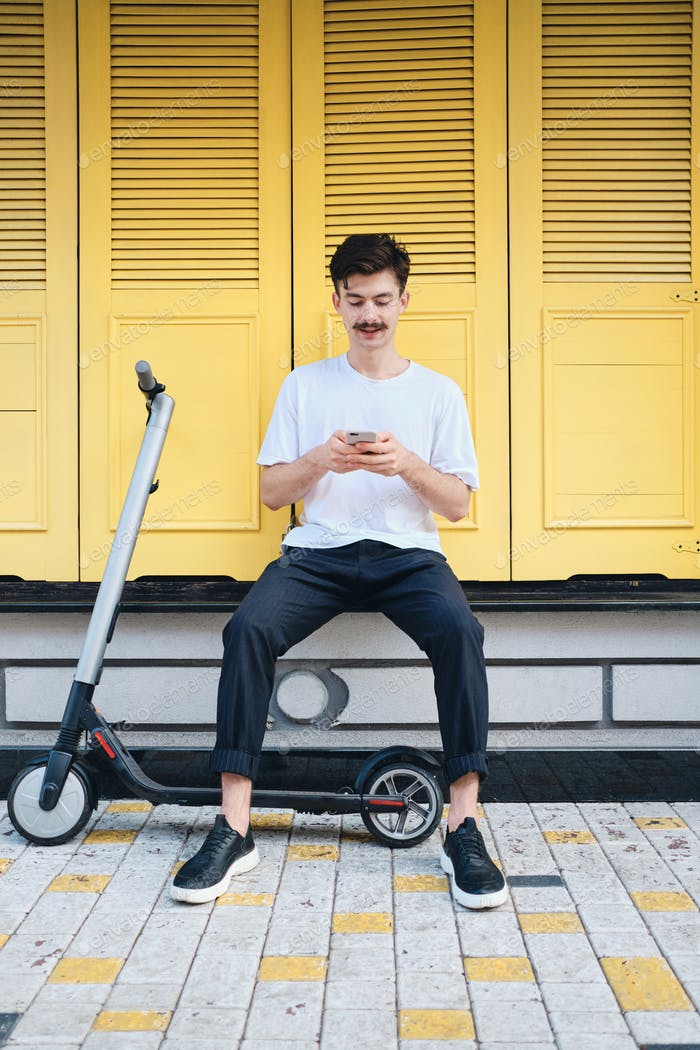 Young attractive mustache man sitting with e-scooter dreamily using cellphone with yellow background