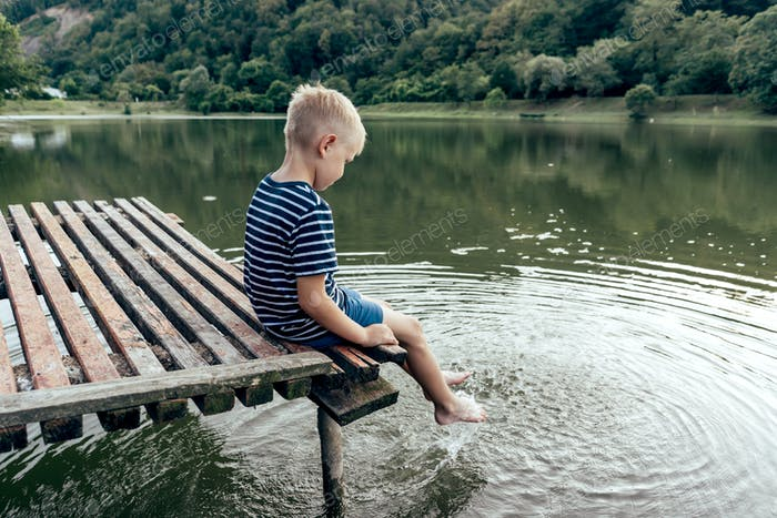 Boy in a summer evening sits on a pier by the lake and wets his feet in the water.