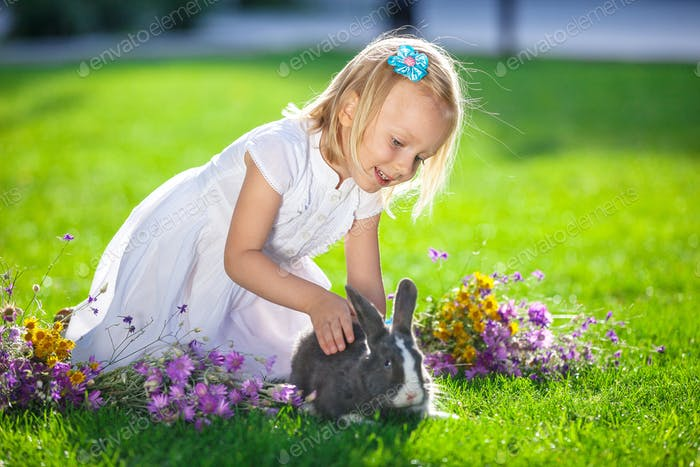 Litte girl stroking pet rabbit outdoors