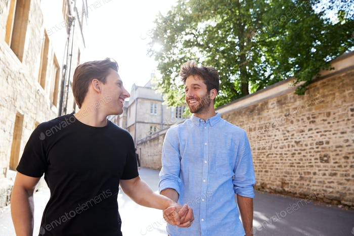 Loving Male Gay Couple On Vacation Holding Hands Walking Along City Street