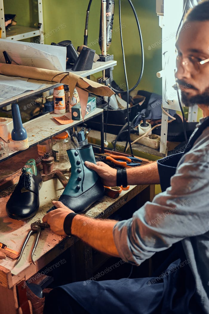 Cobbler is repairing shoes for customers