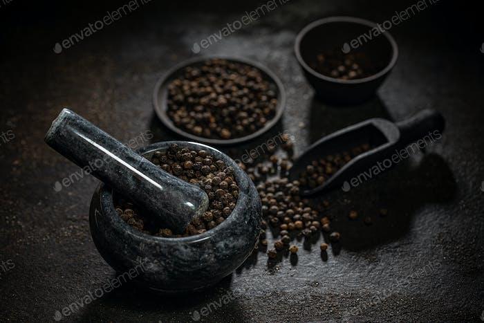 Marble mortar full of black peppercorns