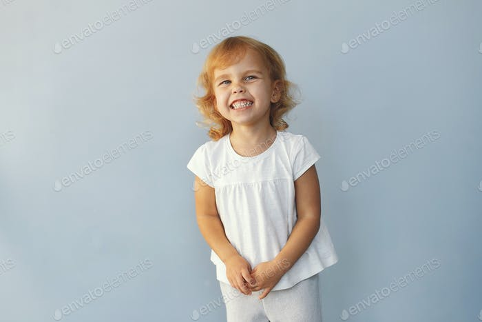 Cute little girl sitting in a studio on a blue background