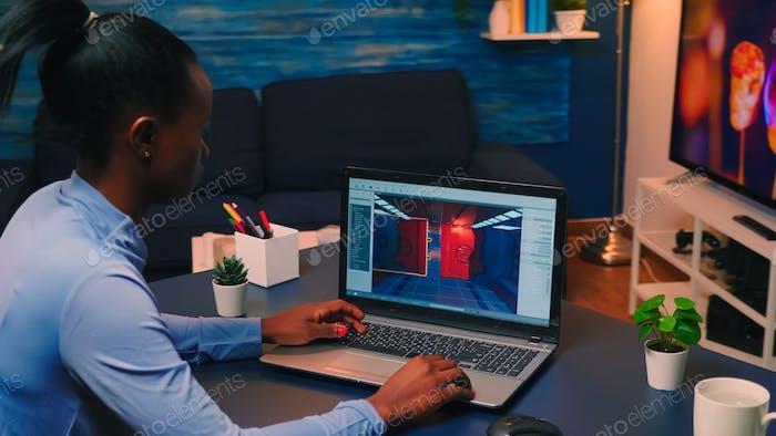 Joven mujer africana jugador prueba juego profesional en línea en el ordenador portátil