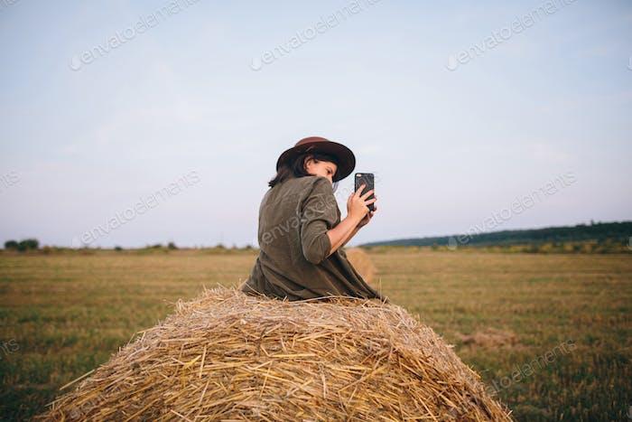 Hermosa mujer elegante sentada en el pajar y tomar fotos de la puesta de sol en el teléfono en el campo de verano.