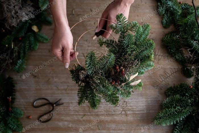 Frau macht Weihnachtskranz aus Fichte, Schritt für Schritt.