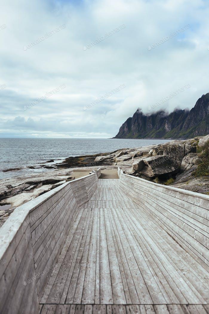 Boardwalk on island against cloudy sky