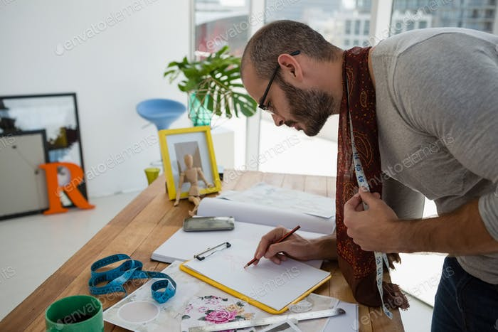 Male designer drawing sketch while standing at table