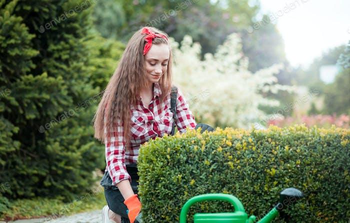 Cheerful gardener woman gardening outdoor
