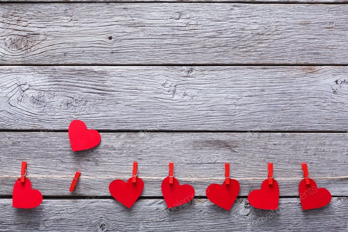 Valentine day background, paper hearts border on wood