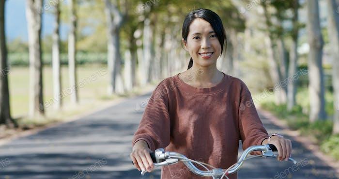 Frau mit dem Fahrrad auf dem Land