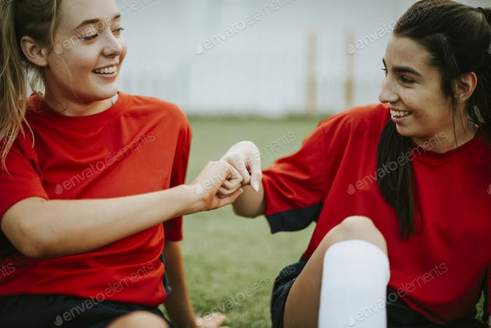 Happy female rugby players doing a fist bump