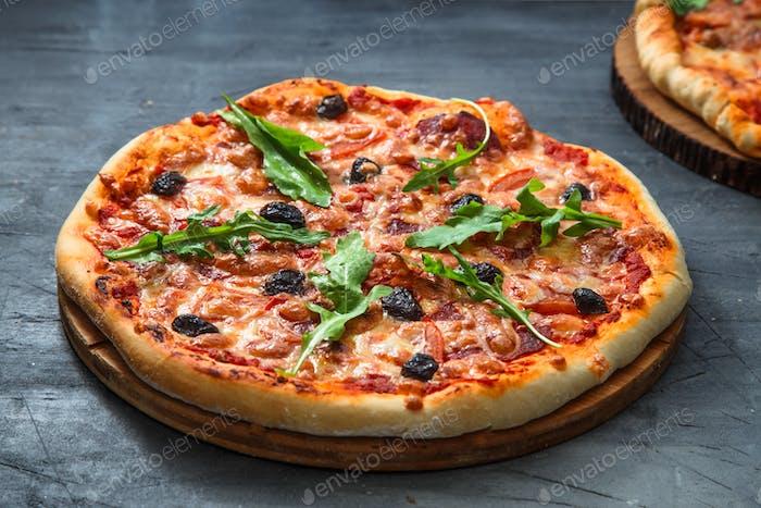 Homemade pizza with tomato, salumi, arugula and olives. Dark background