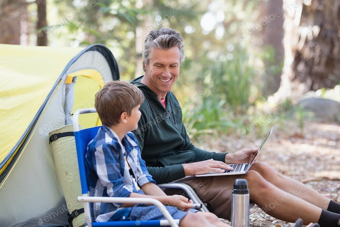 Father talking to son while using laptop in forest