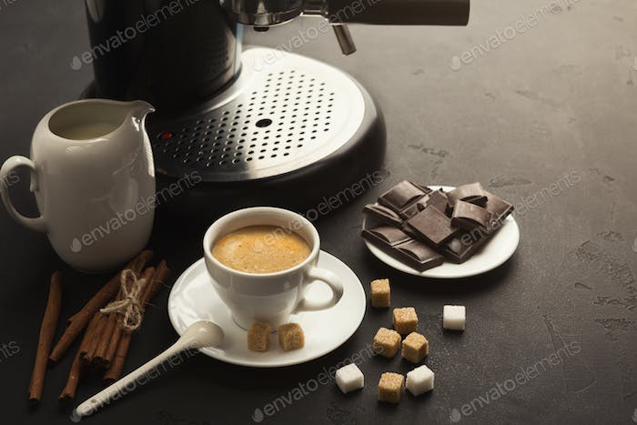 Coffee cup and sweets on black table
