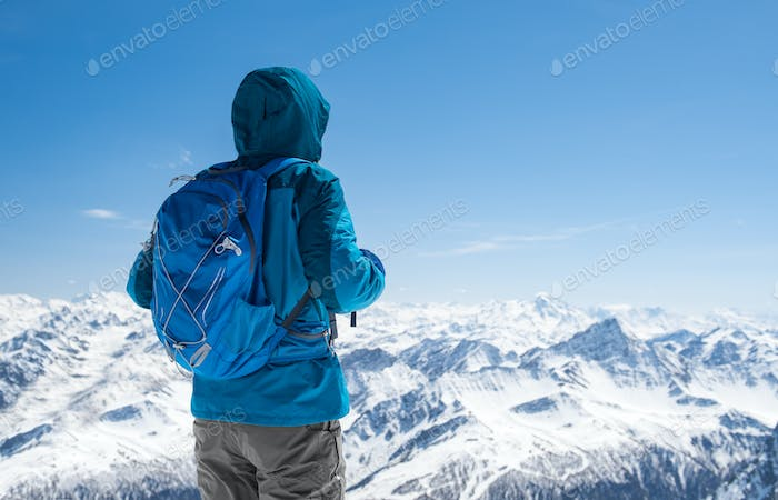 Hiker looking at snowy mountain