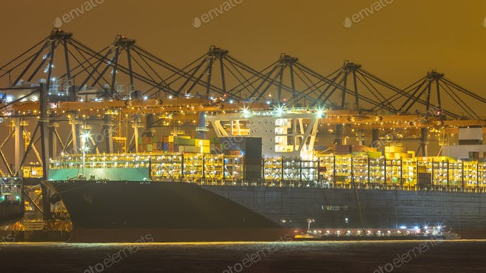Cargo carrier ship being loaded and refueled at night
