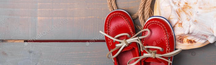 Banner of Red boat shoes near big shell and rope on wooden background.