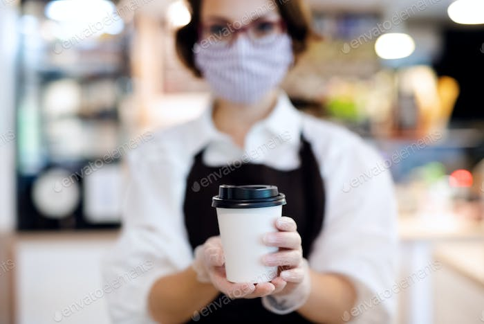 Young woman with face mask working indoors in coffee shop, holding coffee