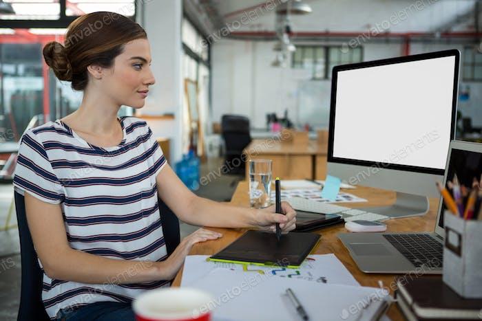Graphic designer using  graphic tablet and desktop