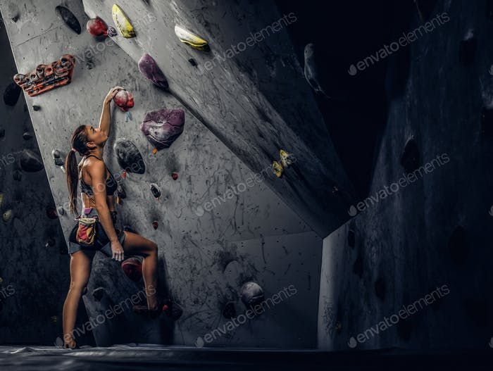 Sporty woman climbing artificial boulder indoors.
