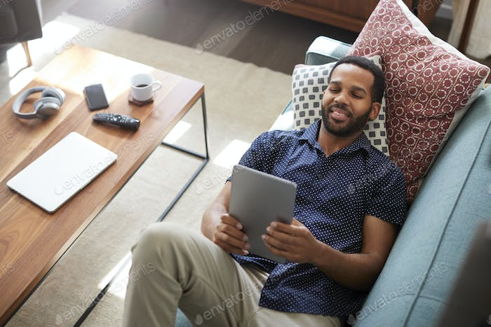 Overhead View Of Man Lying On Sofa At Home Watching Movie On Digital Tablet