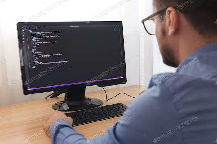 Programmer in Glsses Typing New Lines of HTML Code. Web Design Business and Web Development Concept