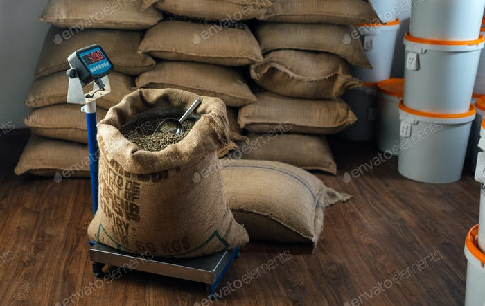 burlap bag with coffee beans and a metal scoop stands on a weighing scale