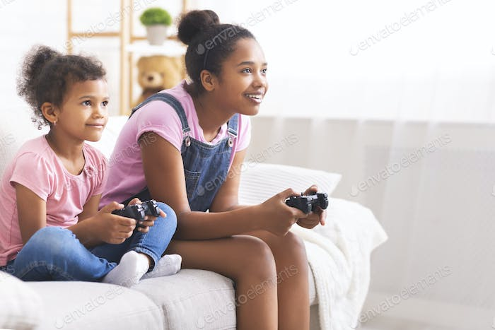 Joyful african american sisters with joysticks playing video games