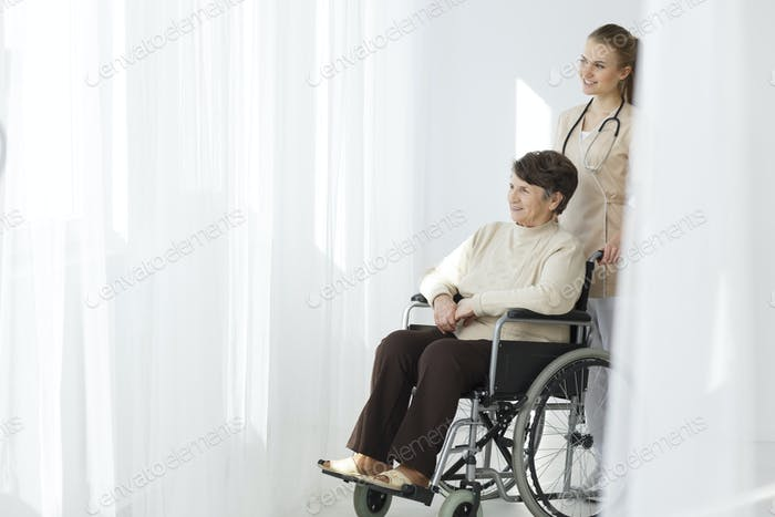 Senior woman on wheelchair and caregiver