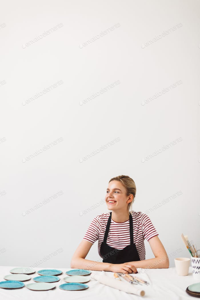 Joyful girl in black apron and striped T-shirt sitting at the table with handmade plates
