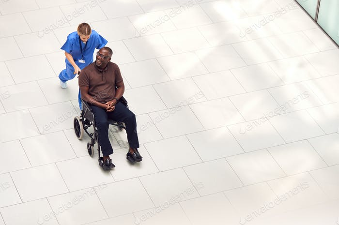Overhead View Of Nurse Wheeling Male Patient In Wheelchair Through Lobby Of Modern Hospital Building