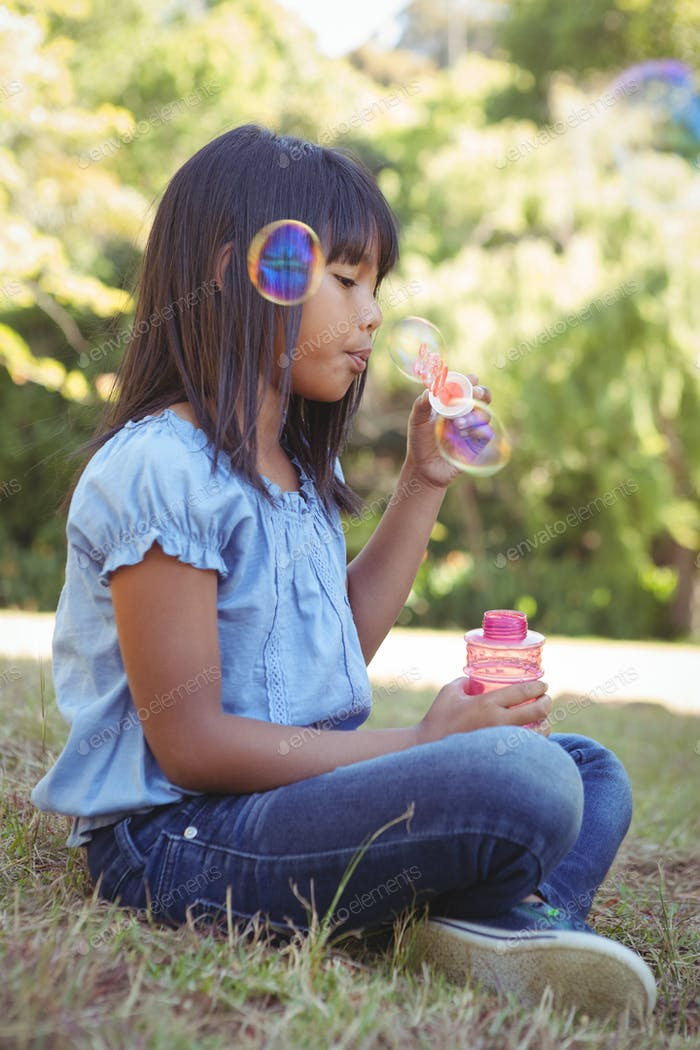 Cute little girl blowing bubbles on a sunny day