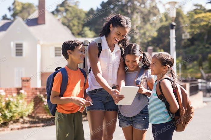 Happy teacher and children using digital tablet on street