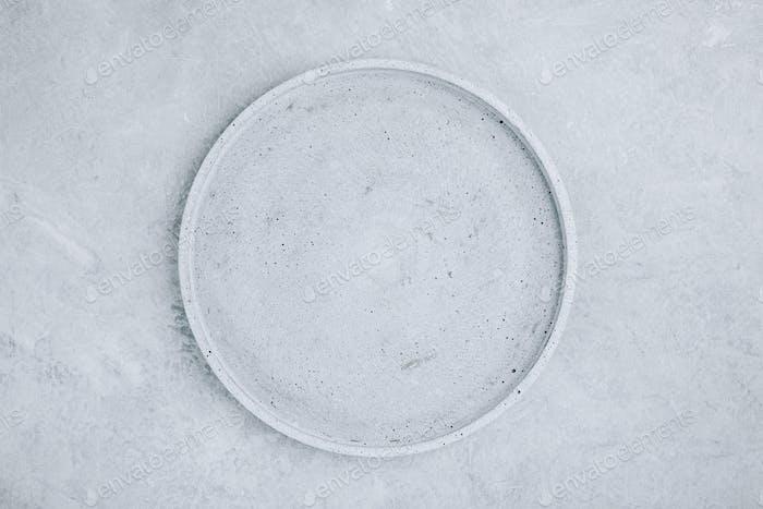 Leere runde Steinplatte auf grauem Betonuntergrund, Draufsicht